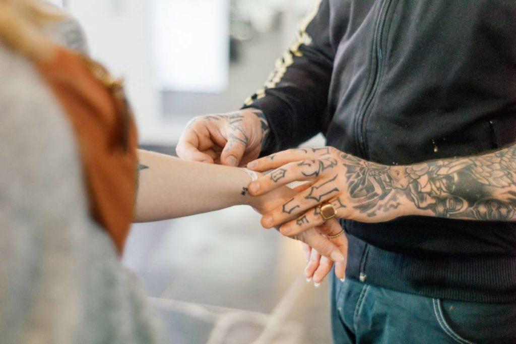 tattoo artist applying a stencil to client's arm