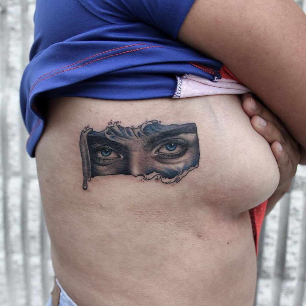 Billie Eilish eye tattoo on Breast (side) - Black and Grey style by Rachel Smith