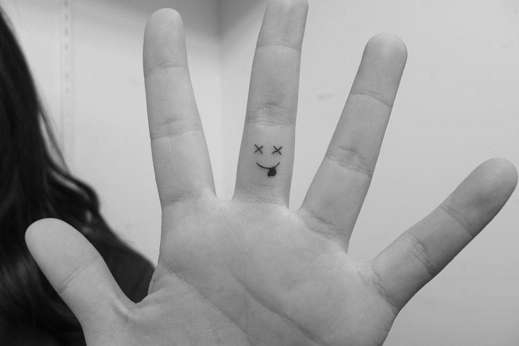 emoji smile  tattoo on Finger by Loko