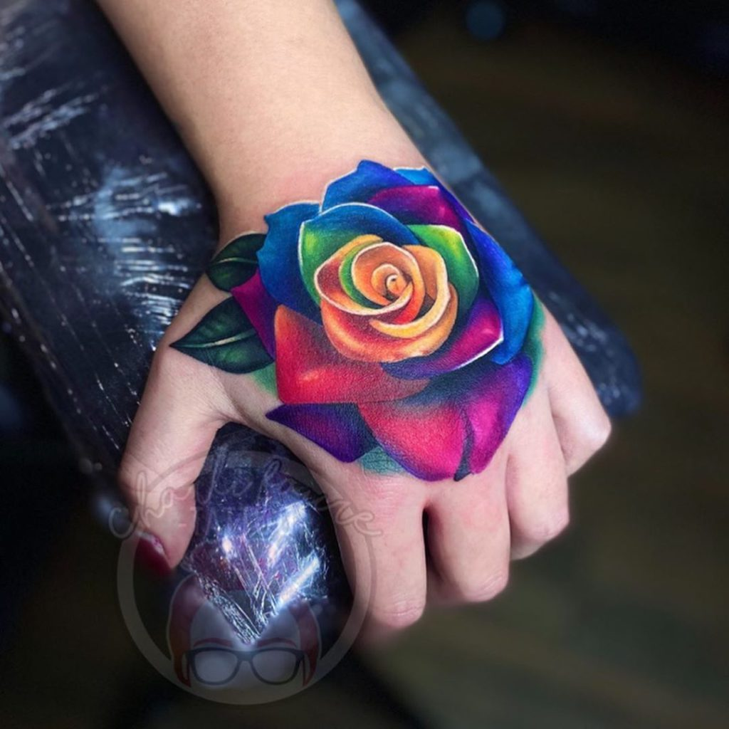 flower botanical rose rainbow tattoo on Hand - Color style by Charli Faure Tattoo